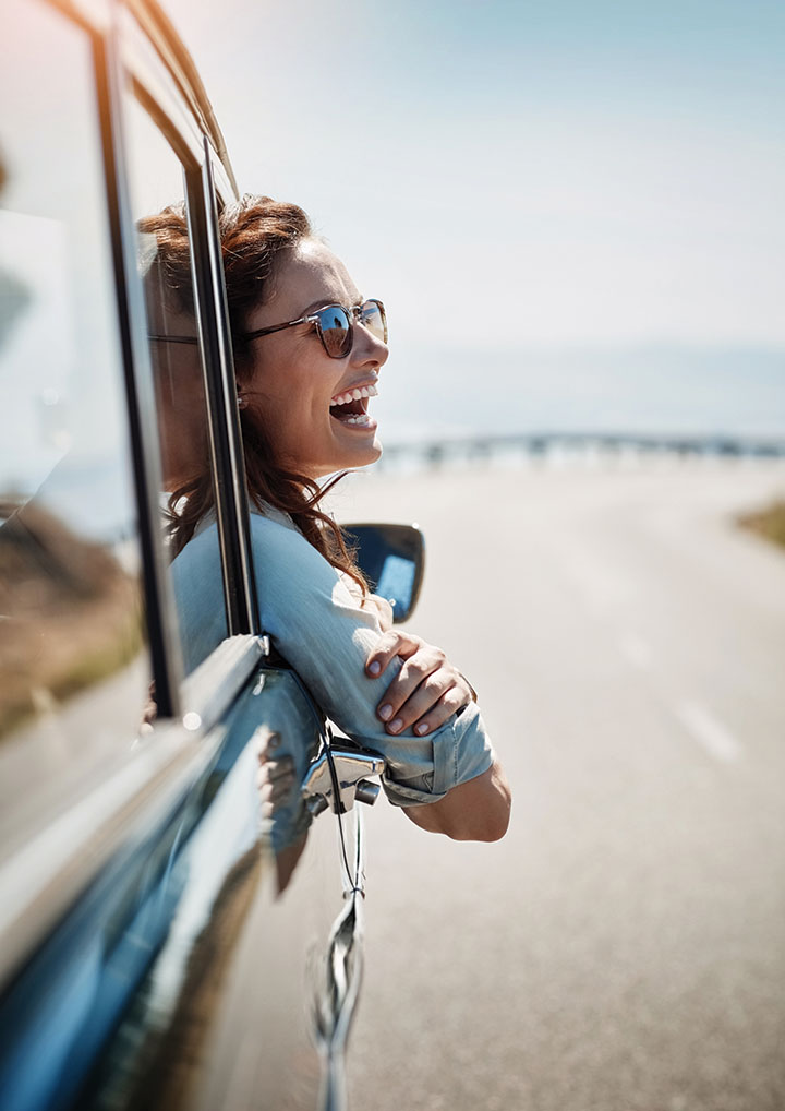 Cropped shot of an attractive woman hanging out of a car window while enjoying a road trip